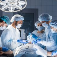 surgeons around a patient in an operating theatre